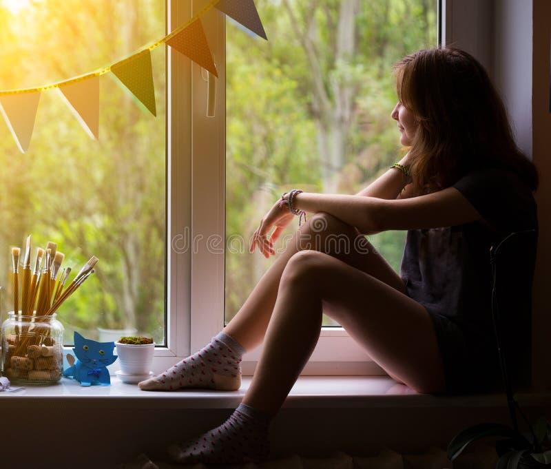 Jugendlich Mädchen, das auf einem Fensterbrett sitzt lizenzfreies stockbild