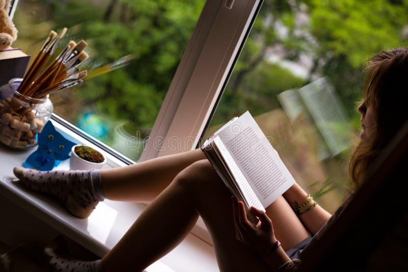 Jugendlich Mädchen, das auf einem Fensterbrett sitzt stockfotografie
