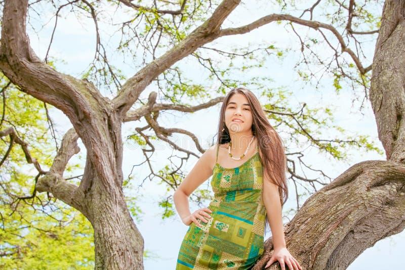 Jugendlich Mädchen, das auf großem Baumast in Hawaii steht lizenzfreie stockfotografie