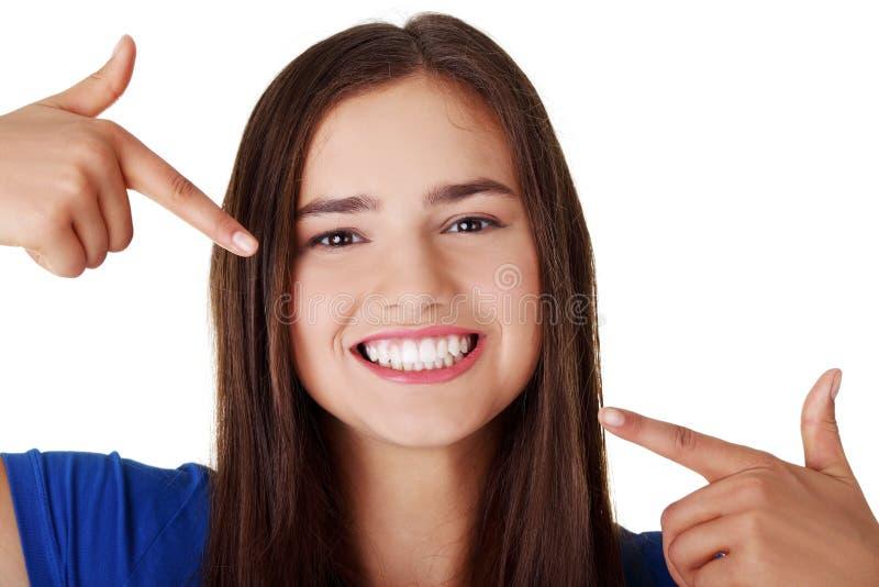 Jugendlich Mädchen, das auf ihre vollkommenen Zähne zeigt stockbilder