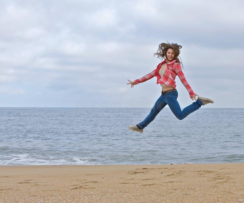 Jugendlich Mädchen, das aufgeregt auf den Strand springt. stockfotos