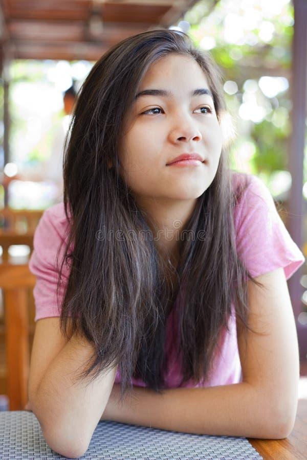 Jugendlich Mädchen, das bei Tisch, denkend sitzt stockbilder