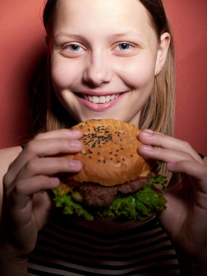 Jugendlich Mädchen, das einen Burger isst stockbilder