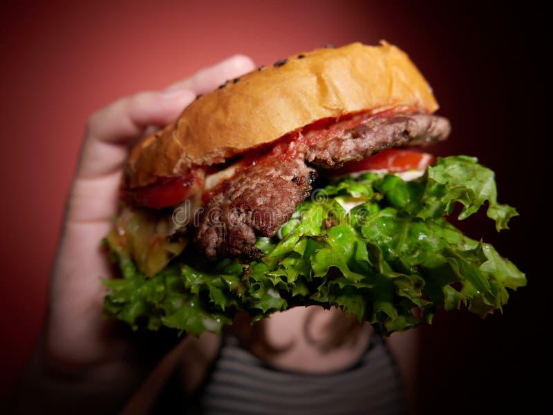 Jugendlich Mädchen, das einen Burger isst stockbild