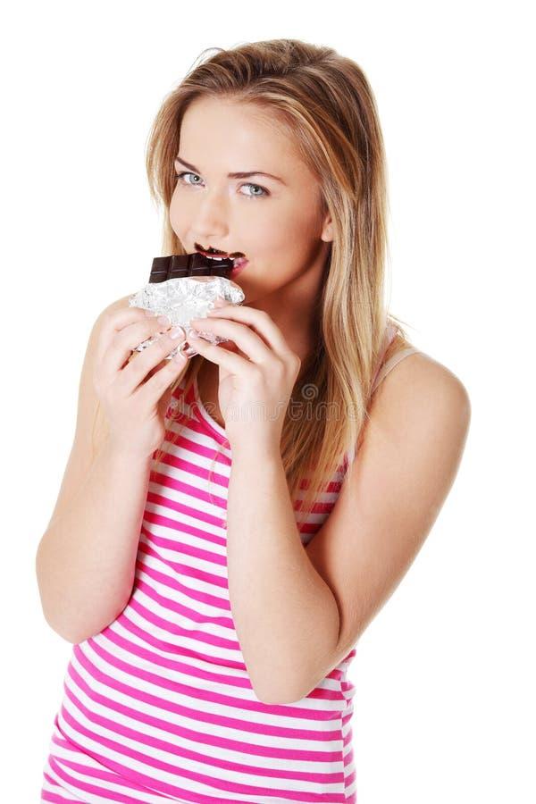 Jugendlich Mädchen, das einen Schokoriegel beißt. lizenzfreie stockfotografie