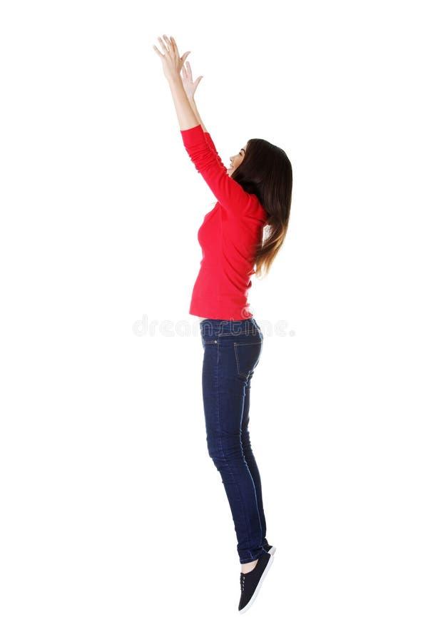 Jugendlich Mädchen, das in einer Luft versucht, etwas abzufangen springt. stockfotografie