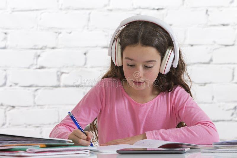 Jugendlich Mädchen, das ihre Hausarbeit mit Musik tut stockfoto