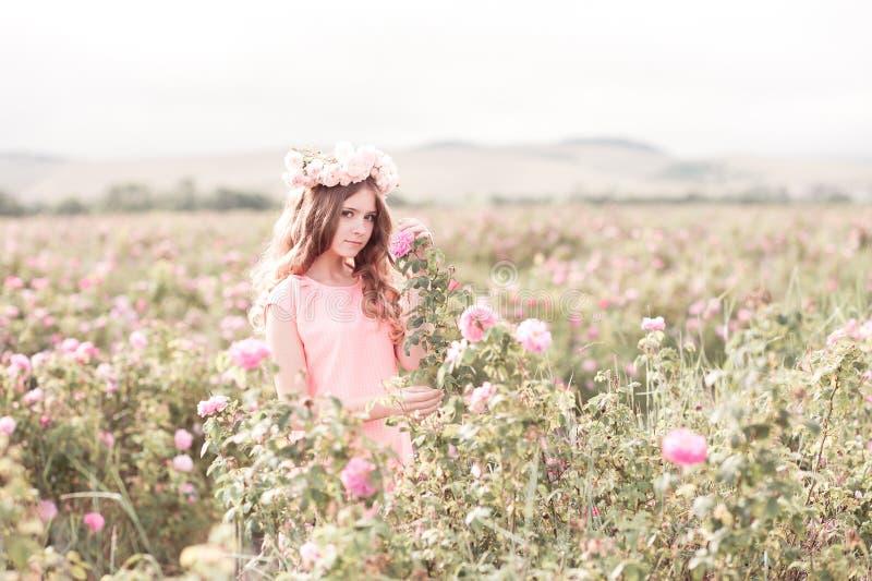 Jugendlich Mädchen, das im Rosengarten steht stockfotos
