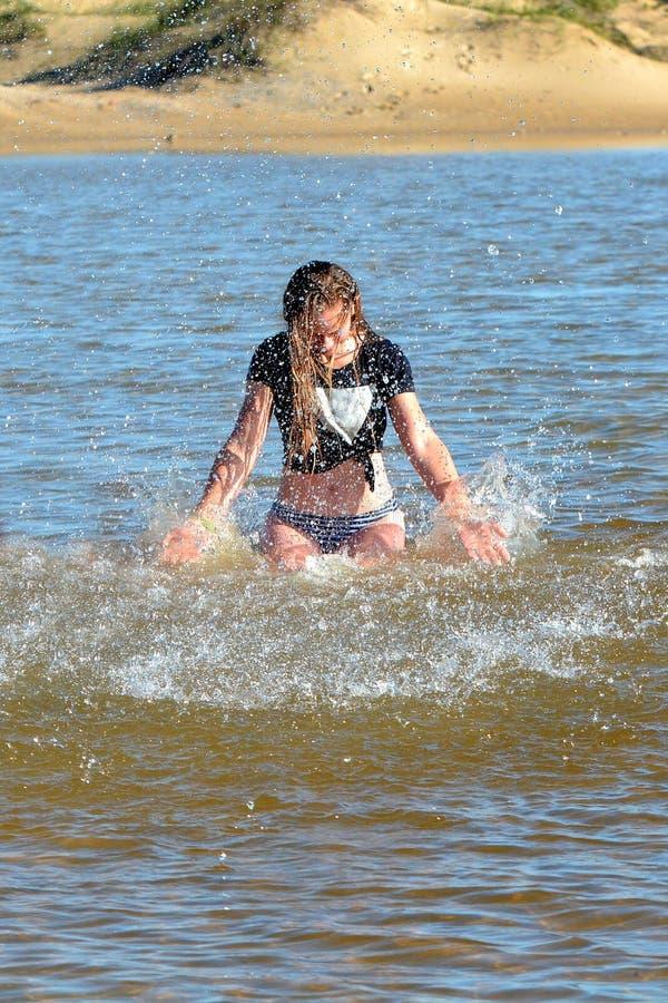 Jugendlich Mädchen, das im Wasser spritzt stockbild