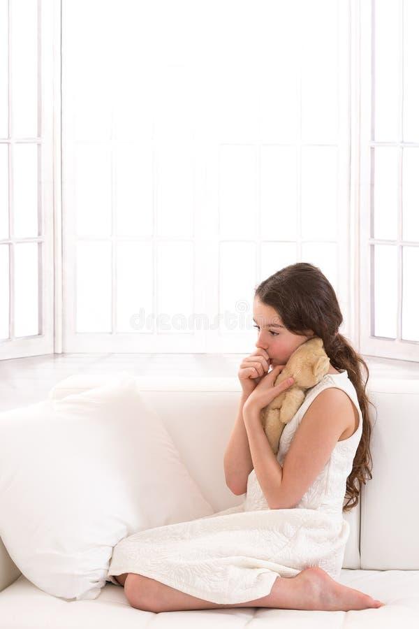 Jugendlich Mädchen, das liebevoll ein Teddybärsaugen hält lizenzfreie stockbilder