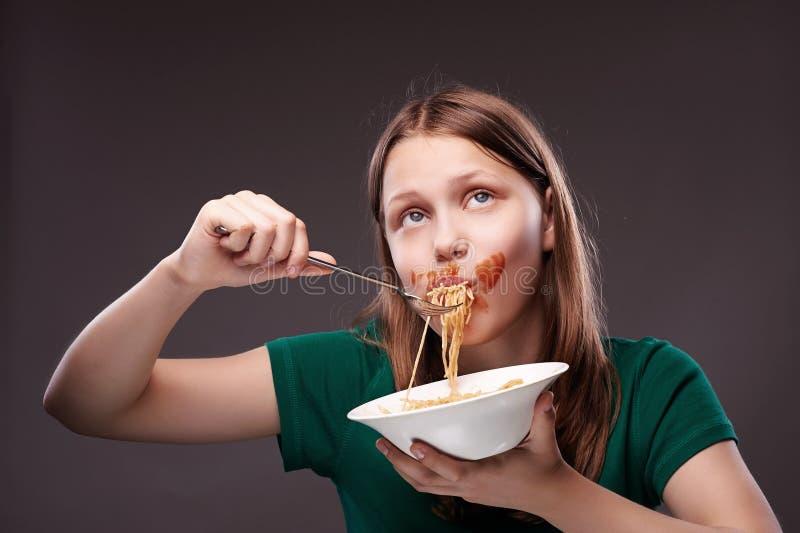 Jugendlich Mädchen, das Teigwaren isst stockbilder