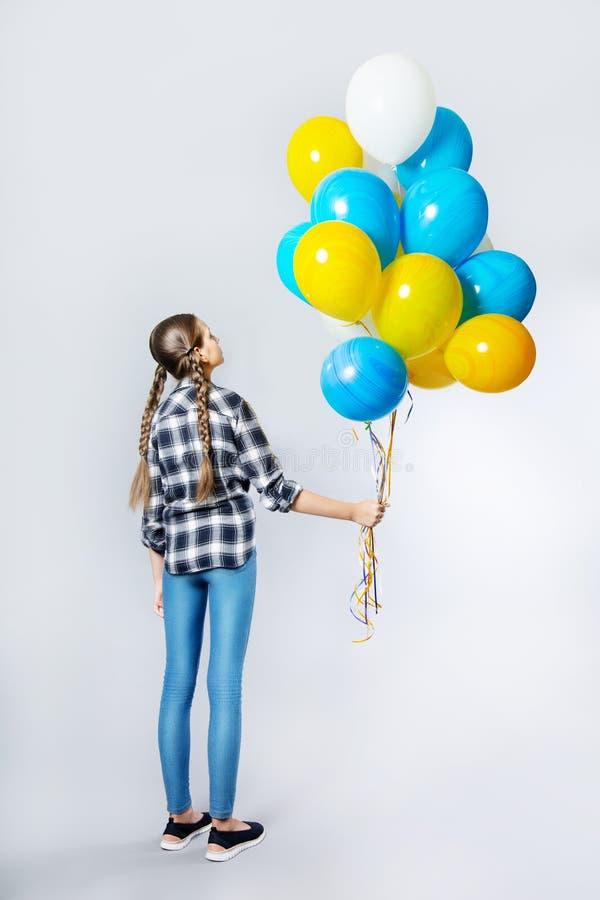 Jugendlich Mädchen, das zurück steht, halten ein Bündel Ballone stockbild