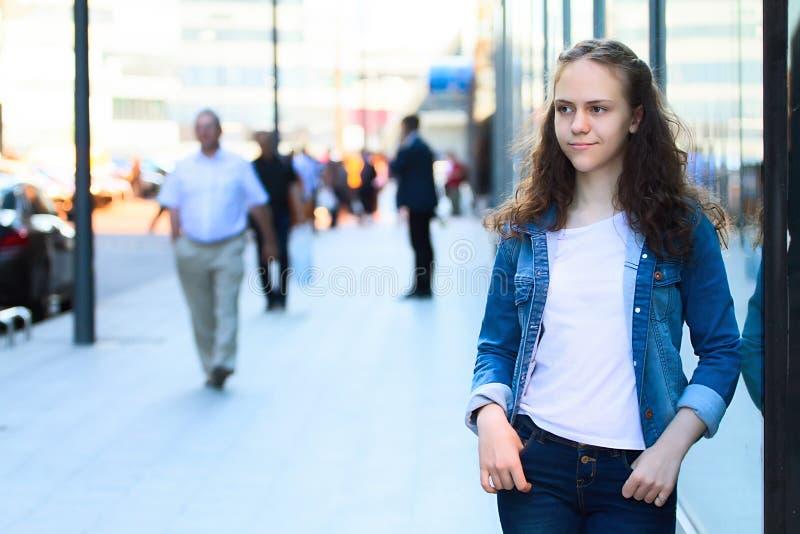 Jugendlich Mädchen in der Denimkleidung steht, lehnend auf einem Glasgebäude auf der Stadtstraße stockfotografie