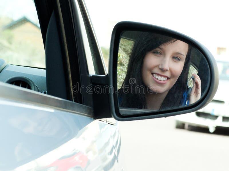 Jugendlich Mädchen des Brunette, das in ihren Autoholdingtasten sitzt stockfotografie