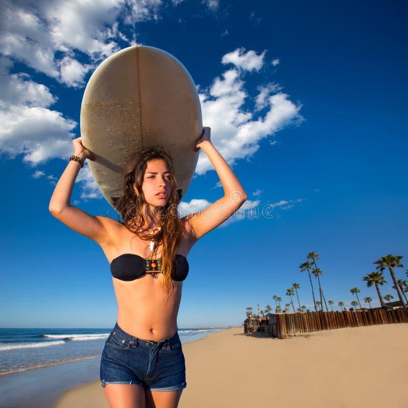 Jugendlich Mädchen des Brunettesurfers, das Surfbrett in einem Strand hält stockbild