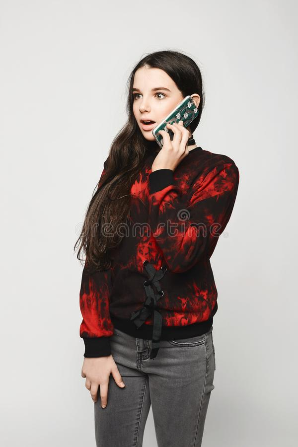 Jugendlich Mädchen des jungen Brunette mit überraschtem Gesicht sprechend am Telefon stockbild