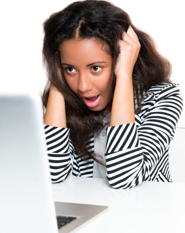 Jugendlich Mädchen des Mischrennens, entsetzt, Laptop betrachtend stockfotos