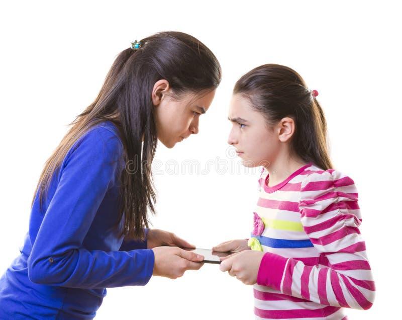 Jugendlich Mädchen, die für digitale Tablette kämpfen lizenzfreies stockbild