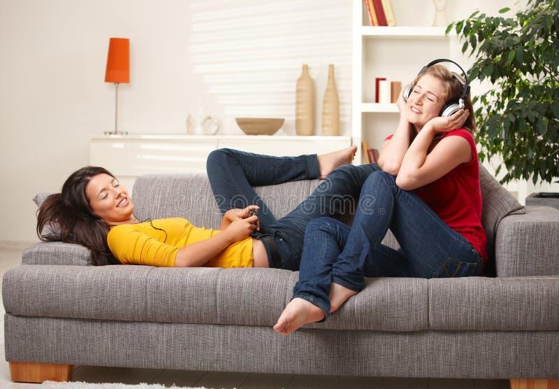 Jugendlich Mädchen, die Musik auf Couch hören stockfotografie