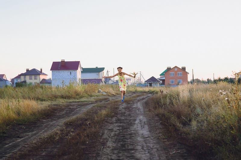 jugendlich Mädchen in einem gelben Kleid, das auf dem Feld, Sommer läuft stockfotos