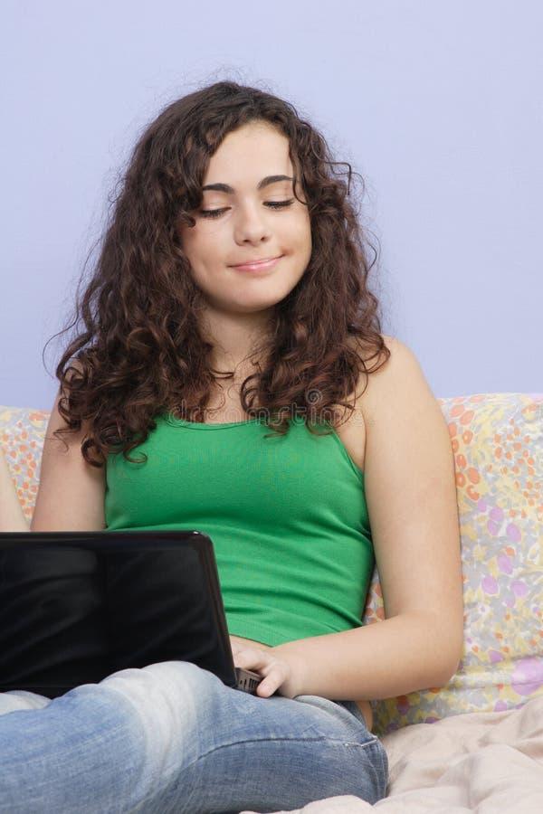 Jugendlich Mädchen im Bett, das auf ihrem Laptop schaut lizenzfreie stockfotos