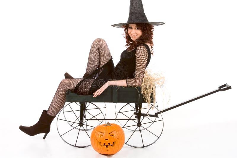 Jugendlich Mädchen im Halloween-Kostüm auf Wagen durch Kürbis lizenzfreie stockfotografie