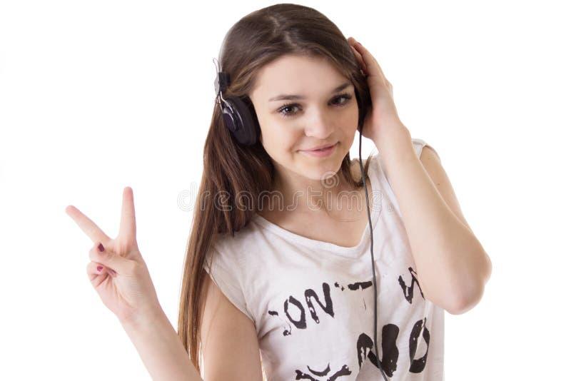 Jugendlich Mädchen mit den Kopfhörern, die Siegeszeichen zeigen lizenzfreie stockfotos