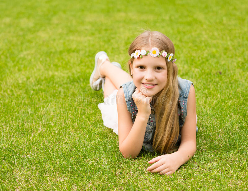 Jugendlich Mädchen mit einem Kranz von den Blumen, die auf einem frischen grünen Gras liegen stockfoto