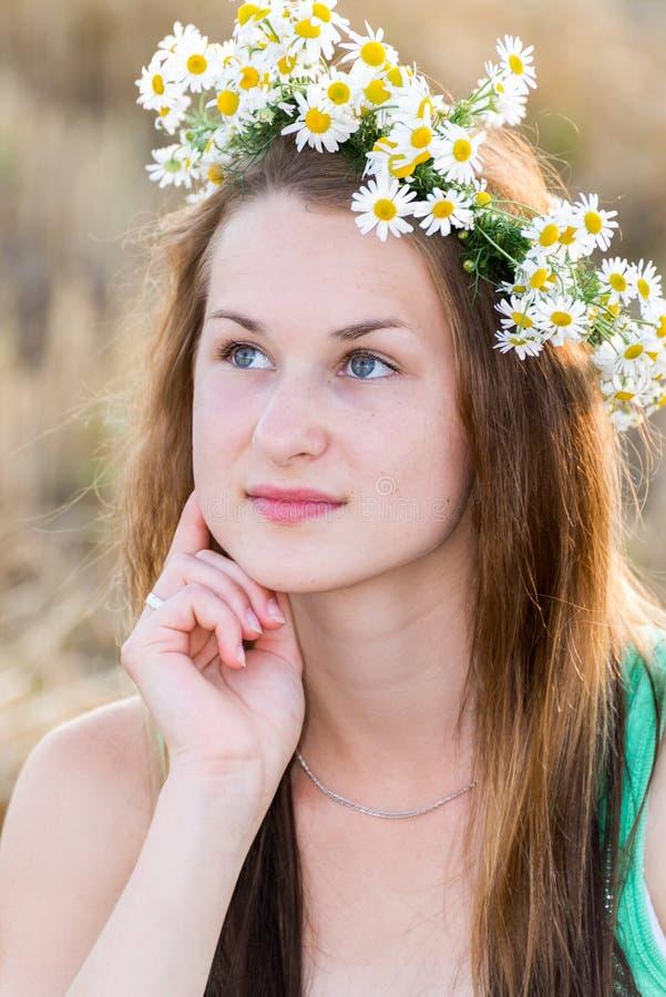 Jugendlich Mädchen mit einem Kranz von Gänseblümchen auf dem Gebiet stockfoto