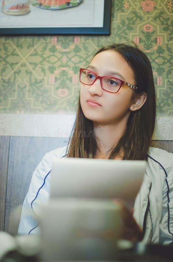 jugendlich Mädchen mit Gläsern macht Skizzen in einem Notizbuch stockfotografie