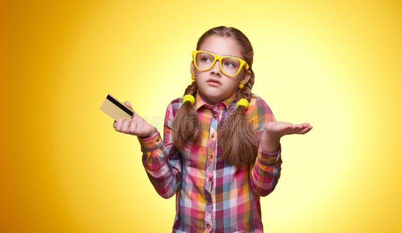Jugendlich Mädchen mit Kreditkarte auf gelbem Hintergrund lizenzfreies stockbild