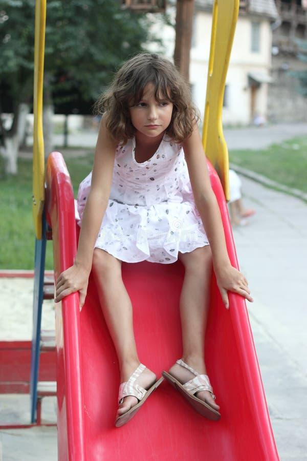 Jugendlich Mädchen schiebt auf children& x27; s-Dia stockbilder