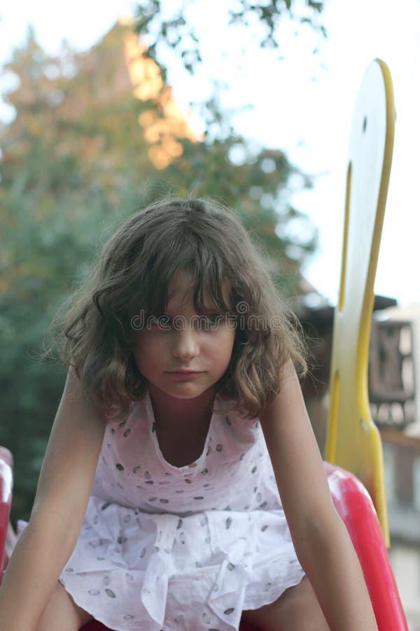 Jugendlich Mädchen schiebt auf children& x27; s-Dia lizenzfreies stockbild
