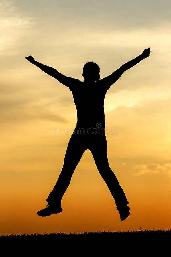 Jugendlich Mädchen springt oben bei Sonnenuntergang lizenzfreie stockbilder