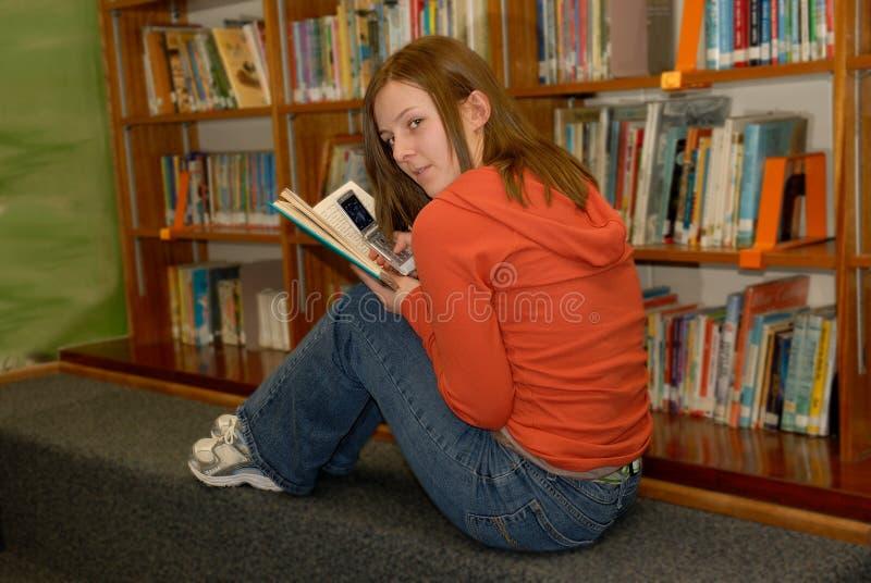 Jugendlich Mädchen in versteckendem Handy der Bibliotheks-2 lizenzfreie stockbilder