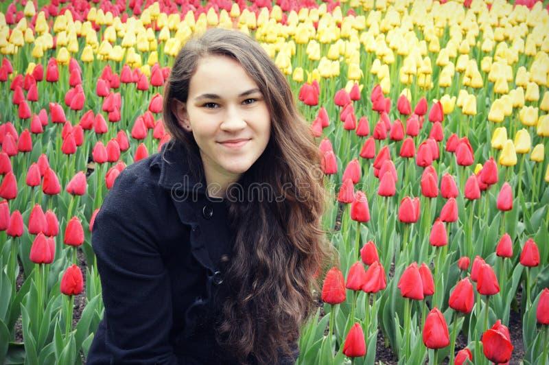 Jugendlich Mädchen vor den roten und gelben Tulpen stockfotografie