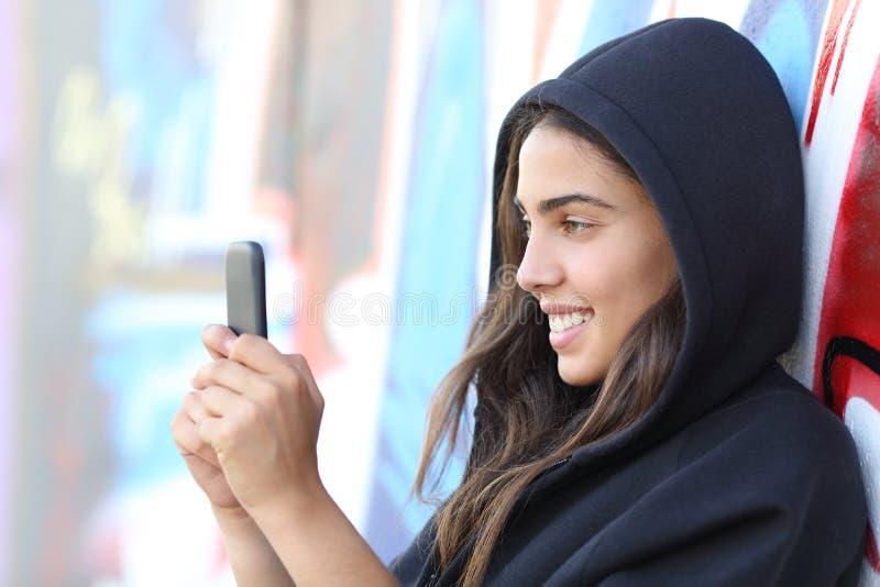 Jugendlich Mädchenablesen der Schlittschuhläuferart glücklich ihr intelligentes Telefon lizenzfreies stockbild