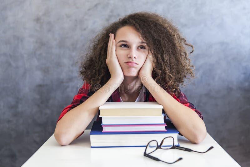 Jugendlich Mädchenrest des gelockten Haares vom Lernen auf Büchern lizenzfreie stockfotos