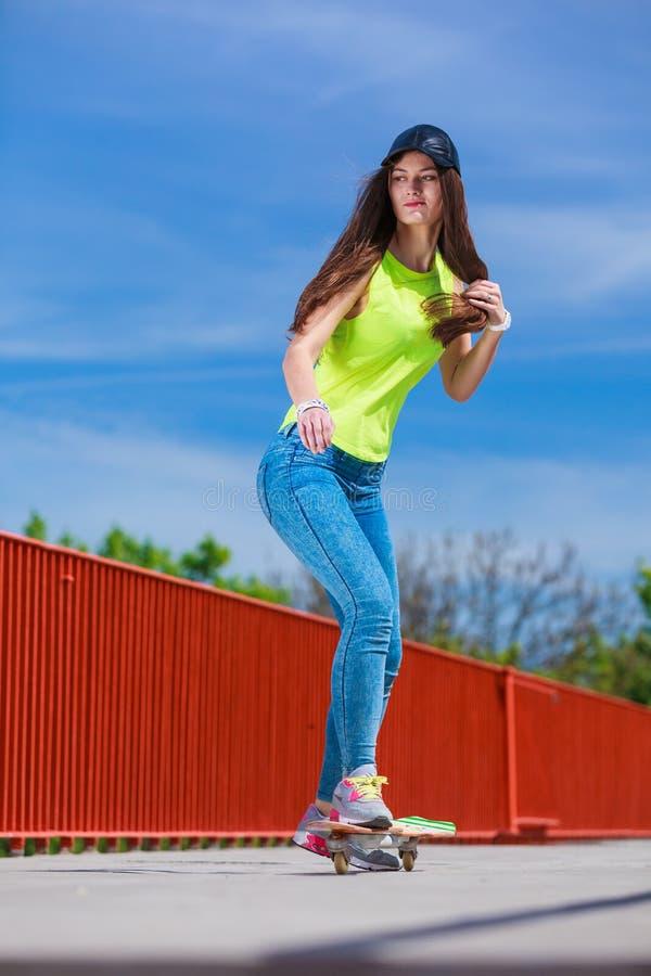 Jugendlich Mädchenschlittschuhläufer-Reitskateboard auf Straße stockbilder