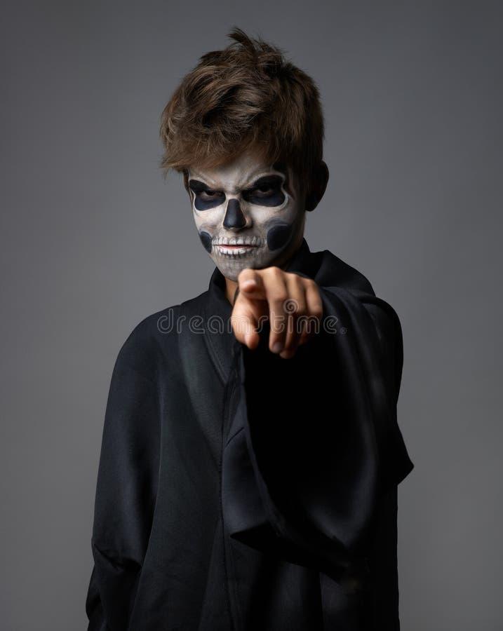 Jugendlich mit dem Make-upschädel zeigt Finger stockfotografie