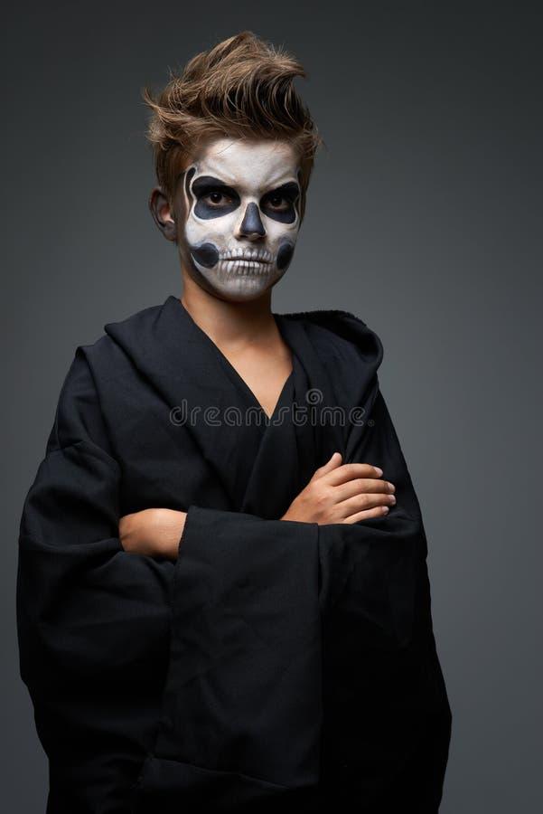 Jugendlich mit Make-up des Schädels im schwarzen Kap lizenzfreie stockbilder
