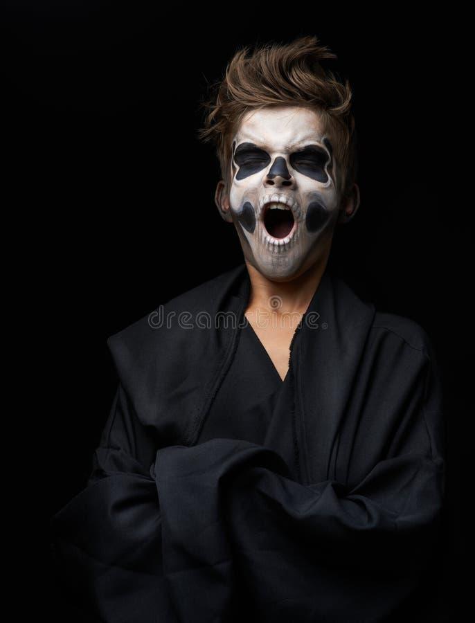 Jugendlich mit Make-up des Schädels im schwarzen Kap gähnt lizenzfreies stockfoto