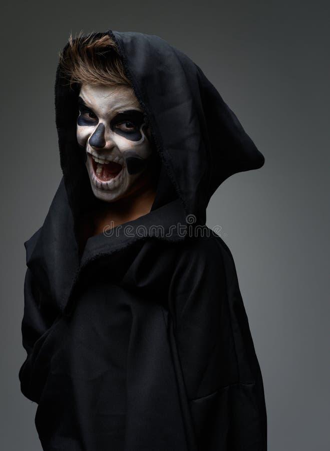 Jugendlich mit Make-up des Schädels im schwarzen Mantel lacht stockfotos