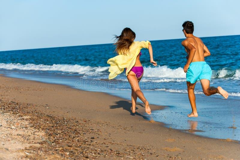 Jugendlich Paare, die auf Strand jagen. lizenzfreie stockfotos