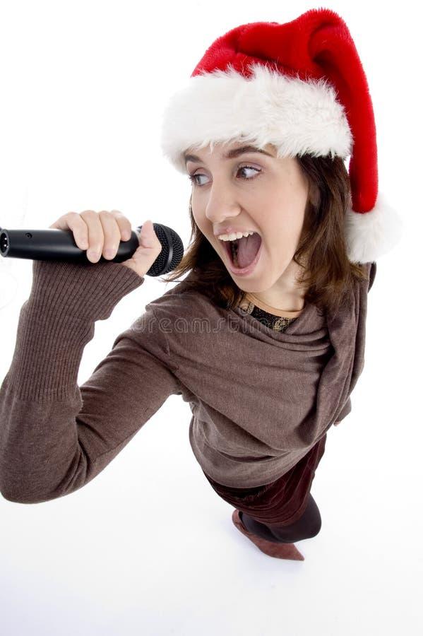 Jugendlich Sänger mit mic und Weihnachtshut lizenzfreies stockfoto