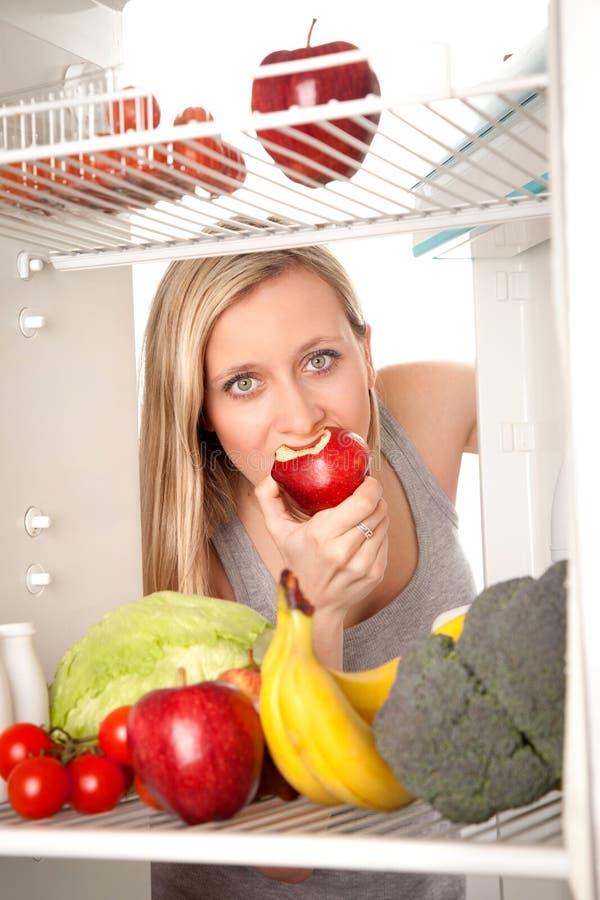 Jugendlich schauende Nahrung im Kühlraum lizenzfreie stockfotos