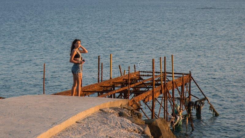 Jugendlich Stellung auf Dock mit verrostetem Herausmetallrahmen stockbilder