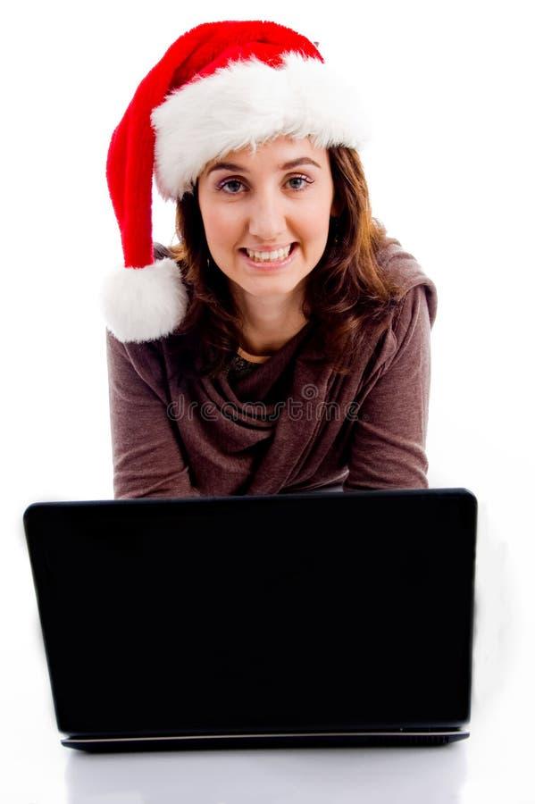 Jugendlich tragender Weihnachtshut, der an Laptop arbeitet stockfotografie