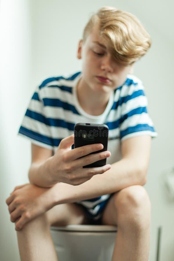 Jugendlich unter Verwendung des Smartphone auf Toilette lizenzfreie stockbilder