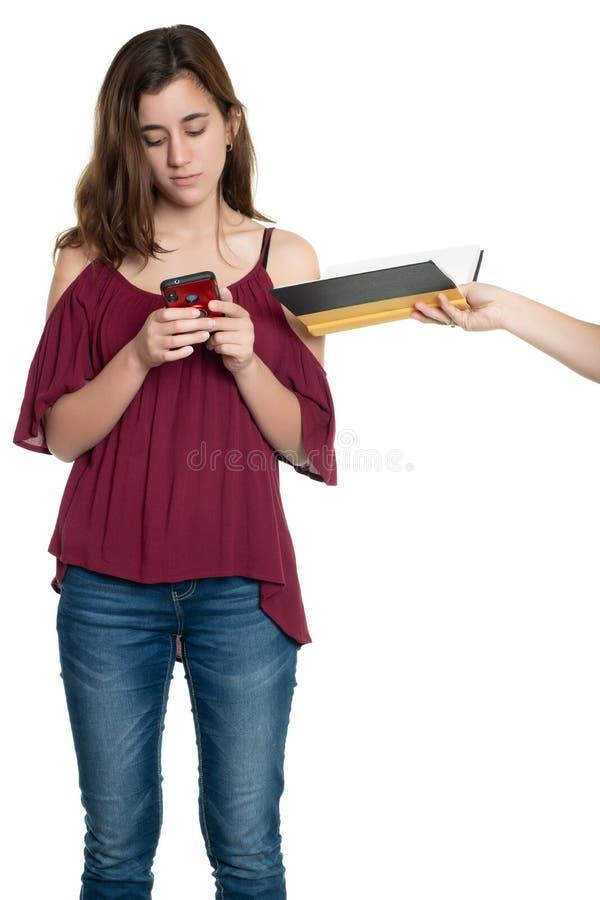 Jugendliche besessen gewesen mit ihrem Smartphone, während eine Hand ihr ein Buch anbietet lizenzfreie stockfotos